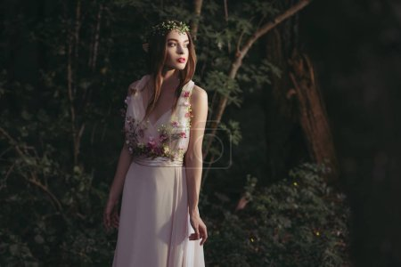 beautiful mystic elf in flower dress and floral wreath in woods