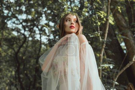 beautiful mystic elf in elegant dress in forest
