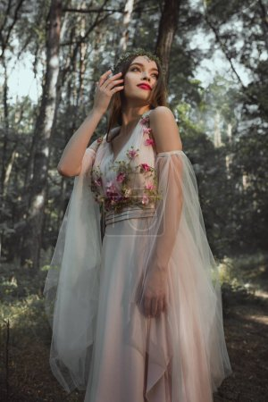 attractive mystic elf in flower dress in forest