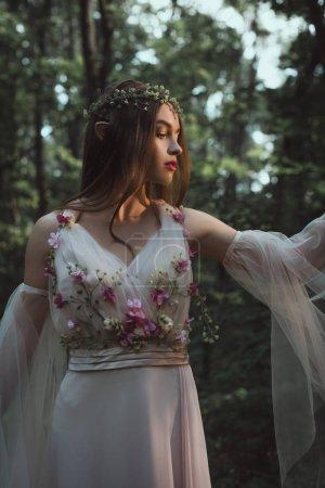Photo pour Elfe mystique en couronne florale et robe avec des fleurs en forêt - image libre de droit