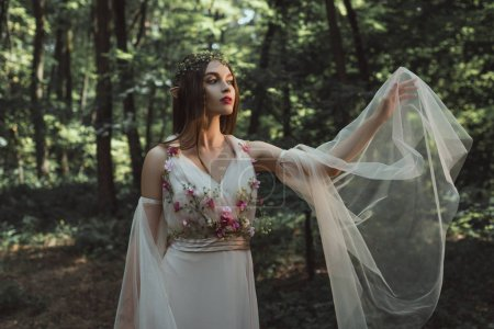 mystic elf in elegant dress with flowers in forest
