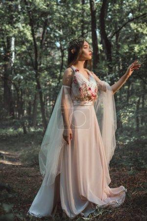 Photo pour Elfe mystique dans le personnage de robe fleur marchant dans bois - image libre de droit