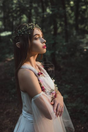attractive mystic elf in flower dress and wreath standing with crossed arms in forest