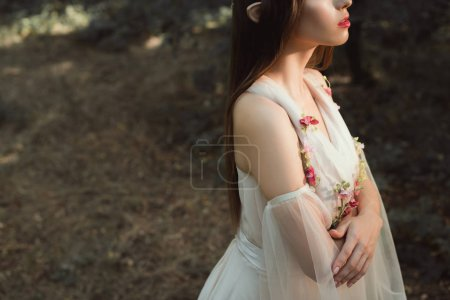 cropped view of elegant elf in dress with flowers standing with crossed arms