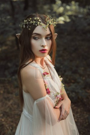 beautiful female elf in flower dress and wreath standing with crossed arms in forest