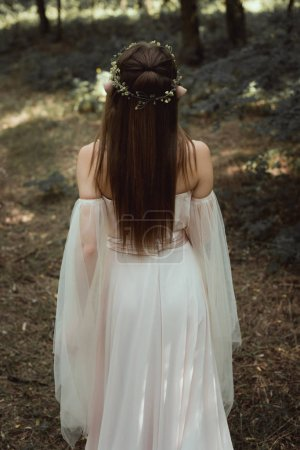 rear view of mystic elf in elegant dress and floral wreath in forest
