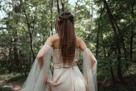 back view of mystic elf in elegant dress in forest