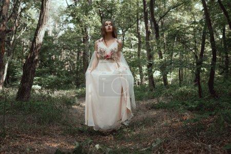 mystic elf in elegant flower dress in forest