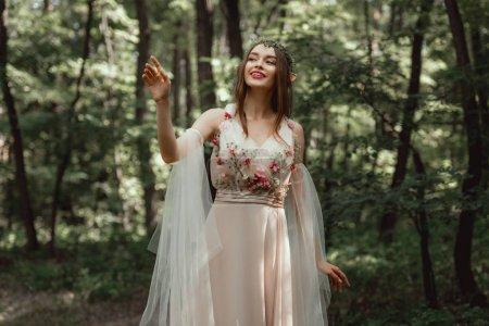 Photo pour Fille elfe heureux dans une élégante robe à fleurs en bois - image libre de droit