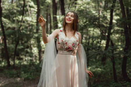 happy elf girl in elegant dress with flowers in woods