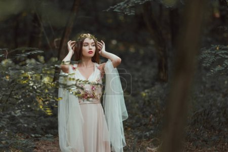 fantasy girl with elf ears in flower dress posing in forest
