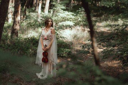 Photo pour Elfe mystique en violon tenue élégante robe en belle forêt - image libre de droit