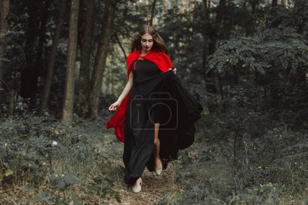 elegant mystic girl in black dress and red cloak running in woods
