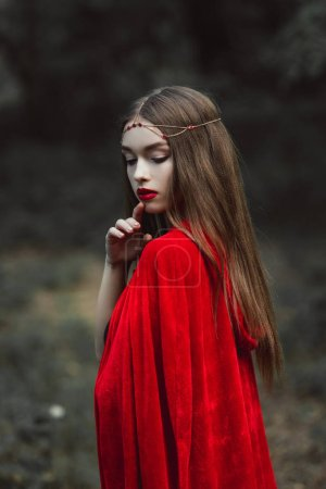mystic girl in red cloak and elegant wreath in forest