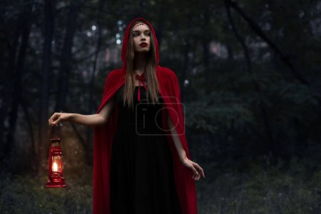 Photo for Elegant mystic girl in red cloak with kerosene lamp walking in dark woods - Royalty Free Image
