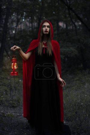young mystic woman in red cloak with kerosene lamp walking in dark woods