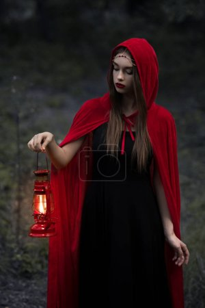 beautiful mystic girl in red cloak walking in dark forest with kerosene lamp