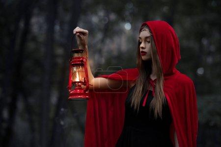mystic girl walking in dark forest with kerosene lamp