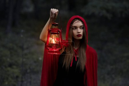 elegant mystic girl walking in dark forest with kerosene lamp