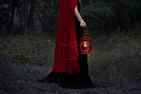 Photo pour Recadrée vue de fille mystique avec lampe au kérosène les balades en forêt noire - image libre de droit