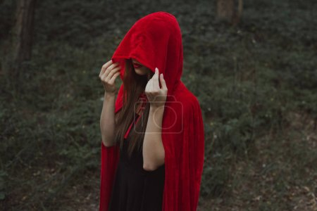 mystic girl in red cloak and hood in forest