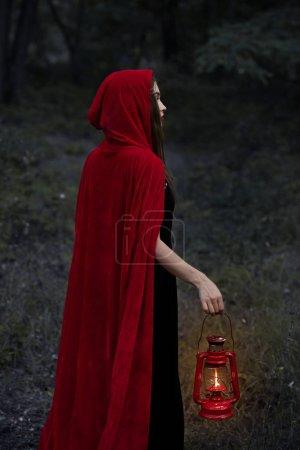 mystic girl in red cloak walking in dark forest with kerosene lamp