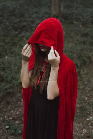 mystic woman in red cloak and hood in dark woods