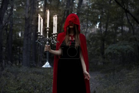 mystic girl in red cloak and hood holding candelabrum with candles in dark forest