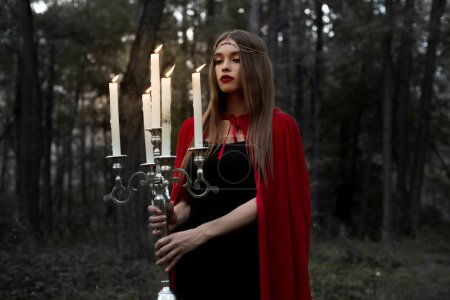mystic girl in red cloak holding candelabrum with flaming candles in forest