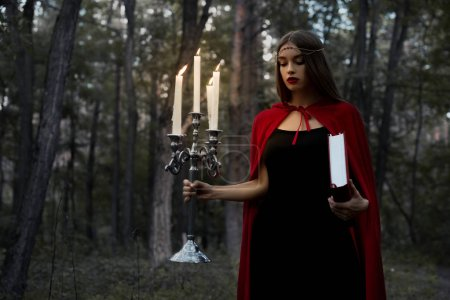 mystic girl in red cloak holding candelabrum with flaming candles and magic book in dark woods
