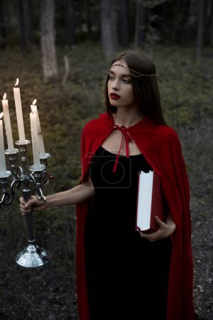 mystic girl in red cloak holding candelabrum with flaming candles and magic book in forest
