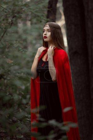 elegant mystic girl in red cloak in woods