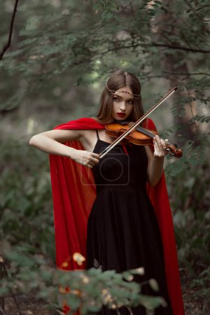 beautiful mystic girl in red cloak playing on violin in dark woods