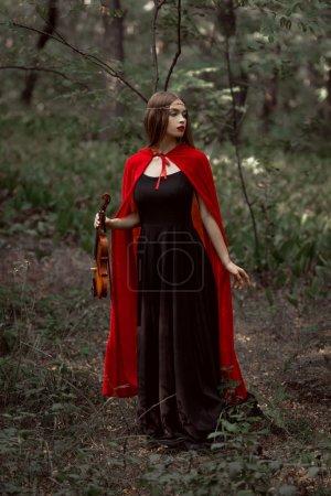 elegant mystic girl in black dress and red cloak holding violin in dark woods