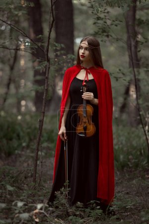Photo for Elegant beautiful woman in black dress and red cloak holding violin in forest - Royalty Free Image