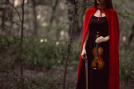 cropped view of elegant woman in red cloak holding violin in dark woods