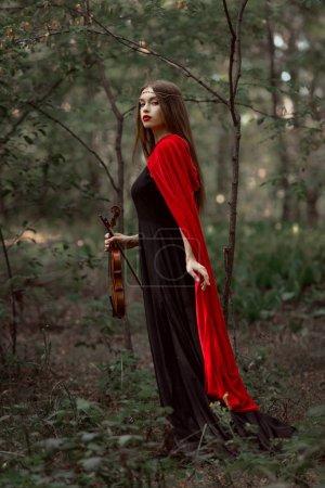 Photo pour Jolie femme mystique, en robe noire et un manteau rouge maintenant violon en forêt - image libre de droit