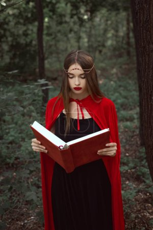 beautiful mystic girl in red cloak and wreath reading magic book in woods