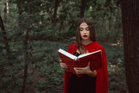 attractive mystic woman in red cloak and wreath reading magic book in forest