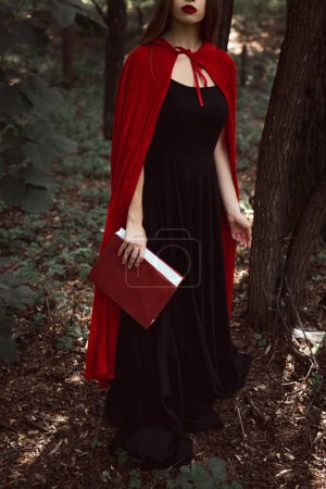cropped view of girl in black dress and red cloak with magic book in forest