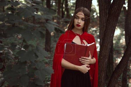 Photo pour Jolie fille dans une cape rouge avec magic book en bois foncé - image libre de droit