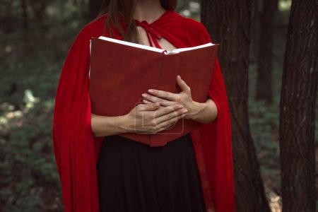 cropped view of mystic girl in red cloak holding magic book in forest