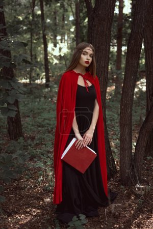 beautiful girl in red cloak with magic book in forest