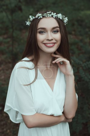 beautiful smiling girl in white dress and floral wreath