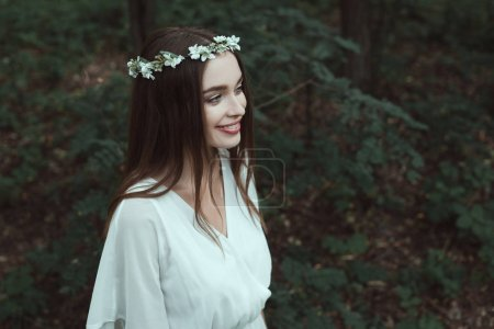 Photo for Stylish smiling girl posing in white dress and floral wreath in woods - Royalty Free Image