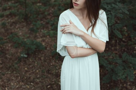 cropped view of tender girl in white dress posing in woods