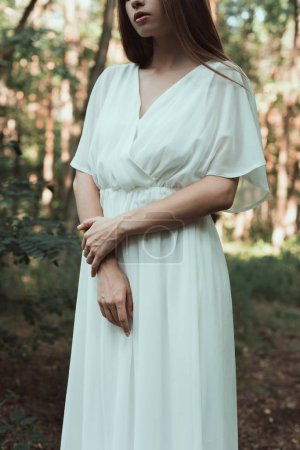 midsection view of elegant tender girl in white dress posing in forest