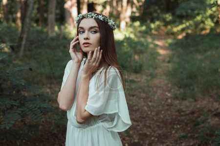 beautiful tender girl posing in white dress and floral wreath in forest