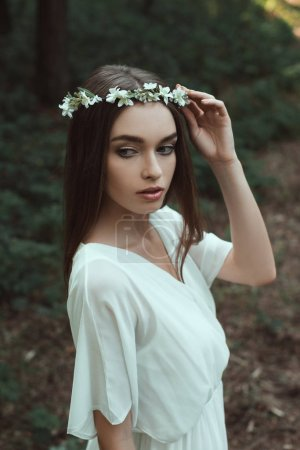young woman posing in white dress and floral wreath in forest