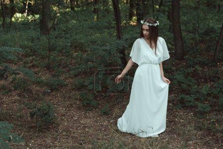 elegantes Mädchen in weißem Kleid und Blumenkranz, das im Wald spazieren geht
